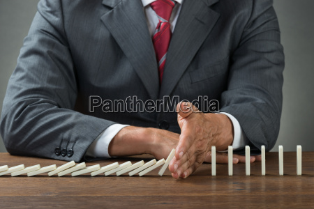 businessman stopping dominoes falling on wooden