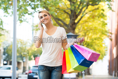 woman using mobile phone while carrying