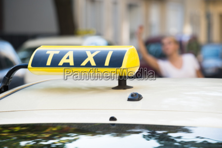 woman raising arm to hail taxi