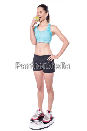 young woman on weigh scale eating
