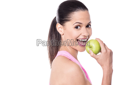 cheerful woman eating fresh green apple