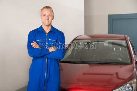 mechanic standing in front of car