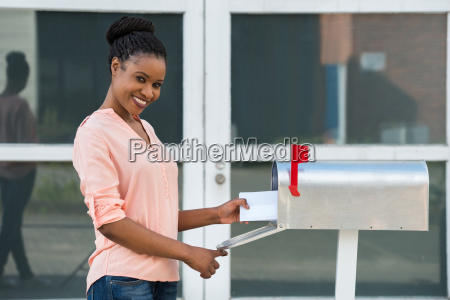 woman collecting her mail from mailbox