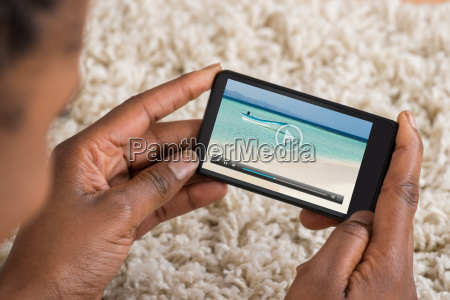 person watching video on mobile phone