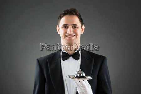happy waiter holding service bell in