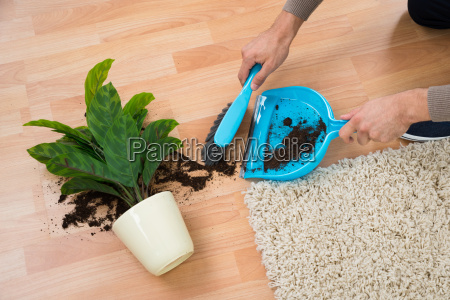 man cleaning mud spilled from potted