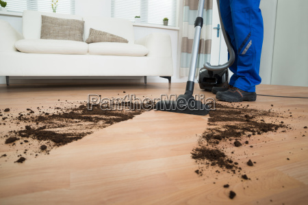 male worker cleaning floor with vacuum