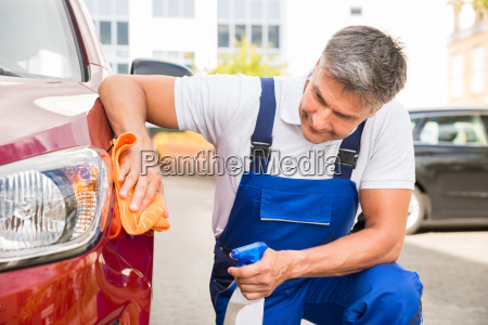 male worker cleaning red car