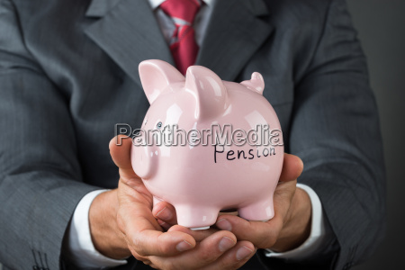 businessman holding piggy bank with pension