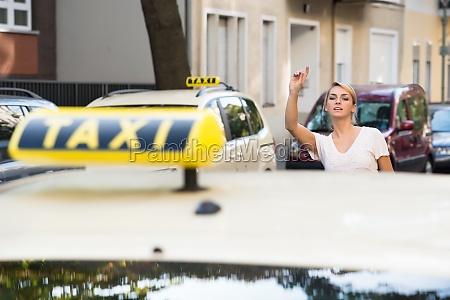 woman raising arm to hail taxi