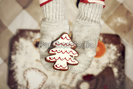 childs hands in gloves holding gingerbread
