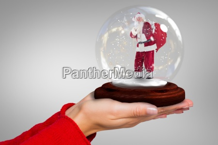 composite image of hand holding santa