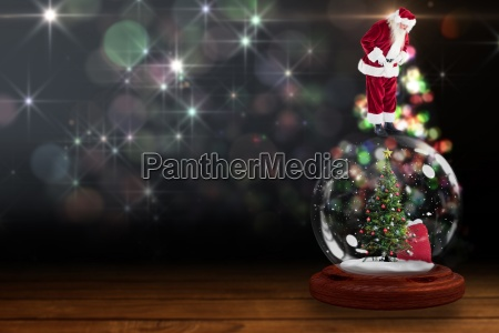 santa standing on snow globe