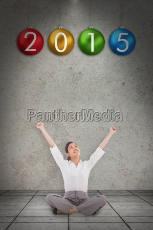 composite image of cheering businesswoman sitting
