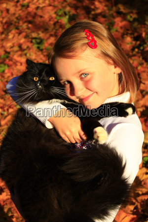 girl embracing with her cat in