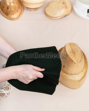 hatter preparing a felt hood for