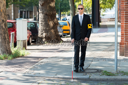 blind man walking on sidewalk holding
