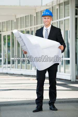 smiling engineer holding blue print