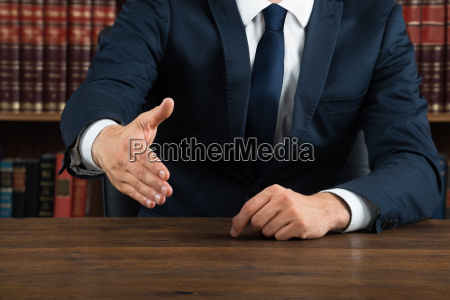 lawyer offering handshake at desk in