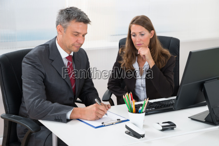 businessman writing on clipboard with assistant
