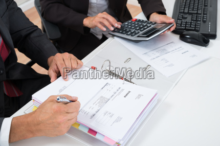 close up of two businesspeople calculating