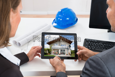 two architects looking at house on