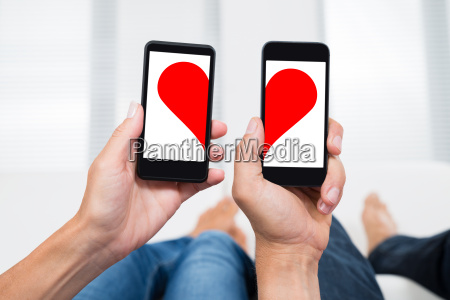 two people with mobile phones showing