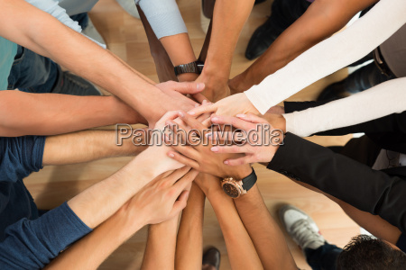 creative business people piling hands over