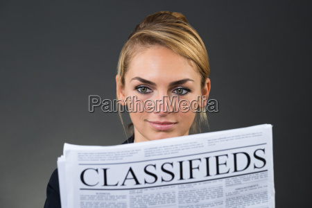 smiling businesswoman reading newspaper