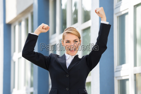 businesswoman raising arms to celebrate success
