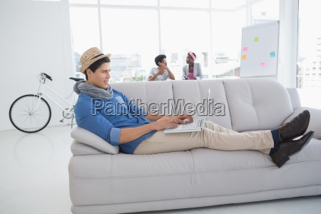 young creative man using laptop on