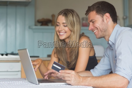 cute couple using laptop together to
