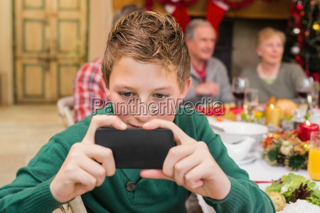 young boy holding smartphone during christmas