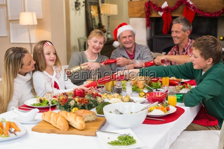 smiling family pulling christmas crackers at