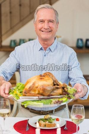 happy mature man holding roast turkey