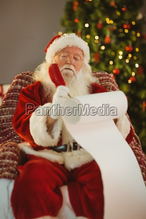 concentrated santa writing his list on