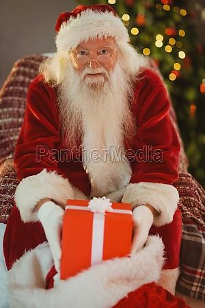 cheerful santa claus holding present