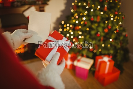 santa claus holding paper and gift