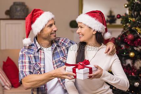 happy couple in santa hat holding