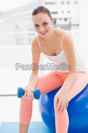 fit brunette lifting blue dumbbell
