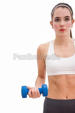 fit brunette holding blue dumbbell