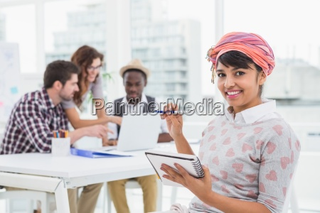 casual businesswoman smiling and taking notes