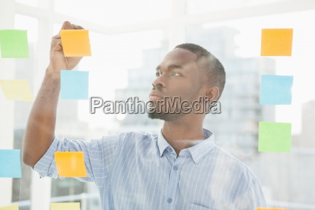 thoughtful businessman writing on sticky notes