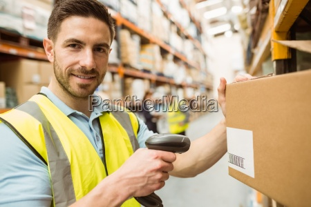 warehouse worker scanning box while smiling