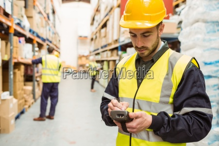 focused worker wearing yellow vest using