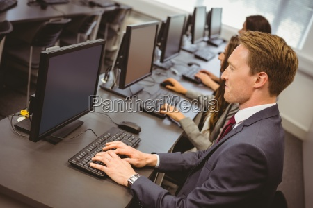 three focused people working in computer