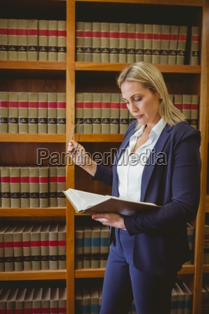 focused librarian reading book and holding