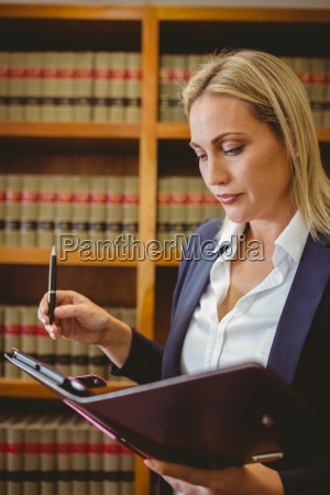 focused female librarian holding textbook