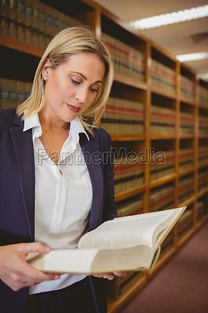 serious librarian reading a book