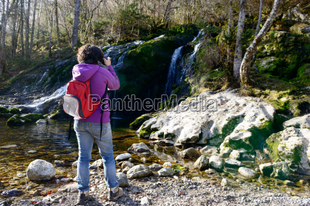 woman photographer photographing a waterfall in